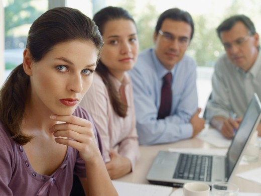 Four businesspeople in boardroom with laptop : Stock Photo