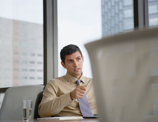 Businessman in boardroom pointing his pen at something : Stock Photo