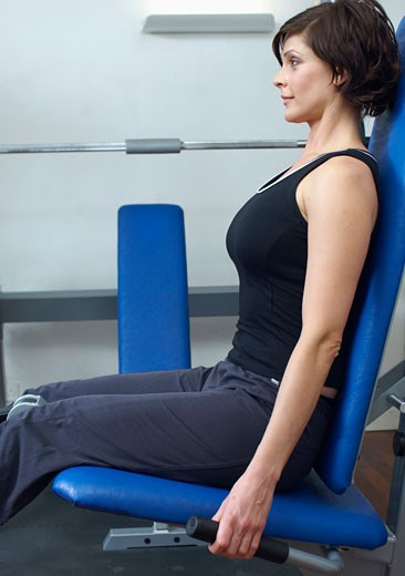 Woman in gym using exercise machine : Stock Photo