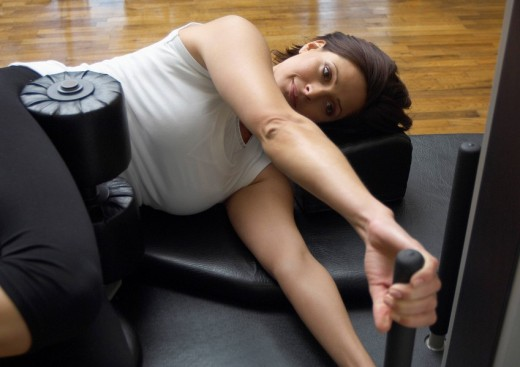 Stock Photo: 1775R-9888 Woman in gym using exercise machine