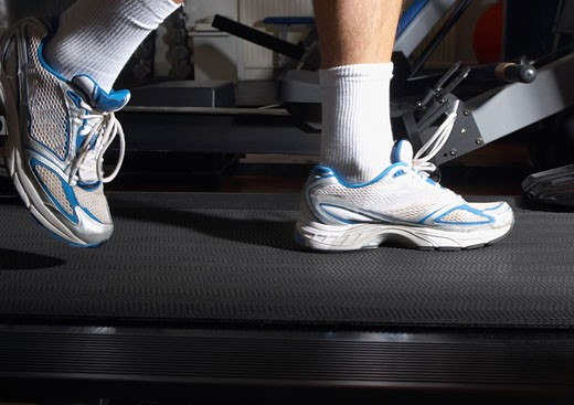 Stock Photo: 1775R-9892 Man´s feet on a treadmill in a gym