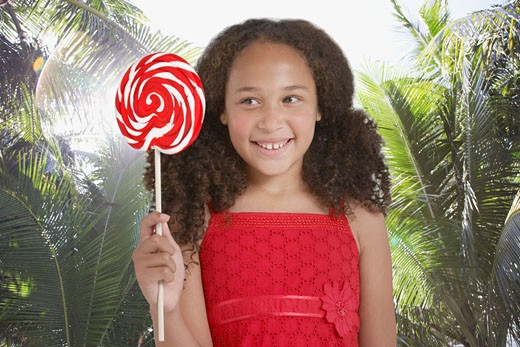 Young girl outdoors holding lollipop : Stock Photo
