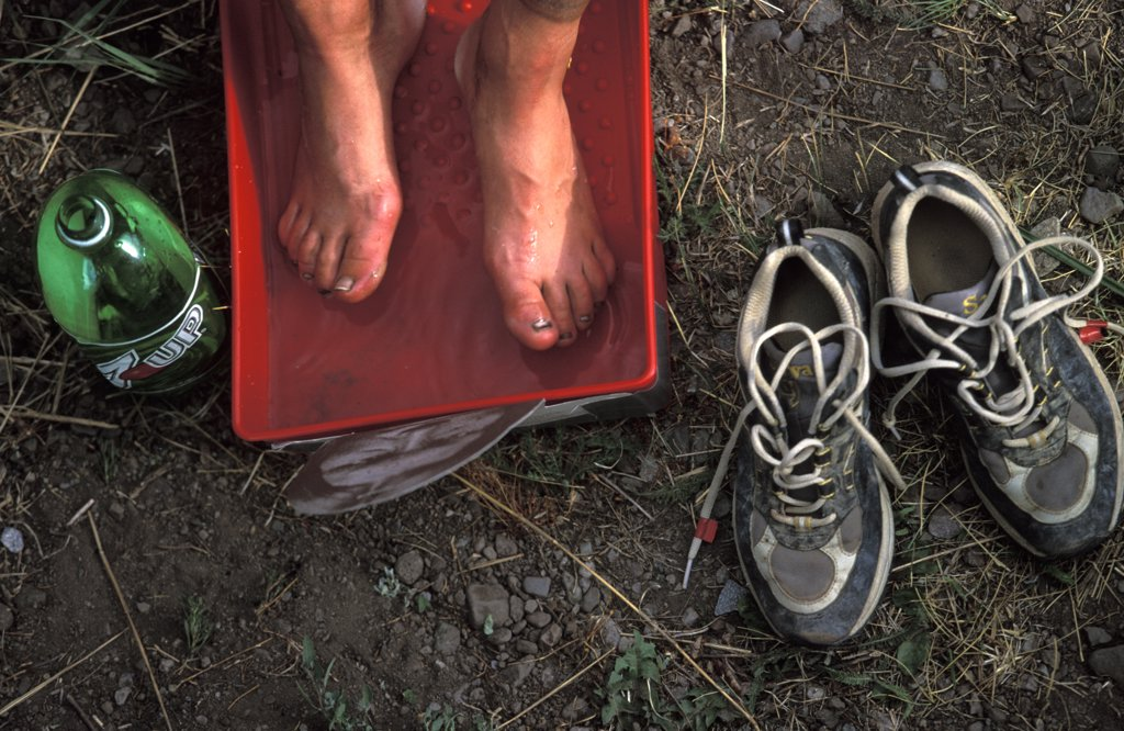 Stock Photo: 1778-10180 A sore pair of feet rest in a footbath after the trekking leg of an adventure race