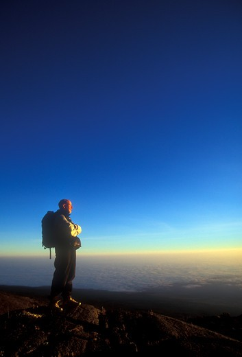Stock Photo: 1778-10351 A man stands alone at sunrise as he looks down to the Tanzanian plains below Mount Kilimanjaro