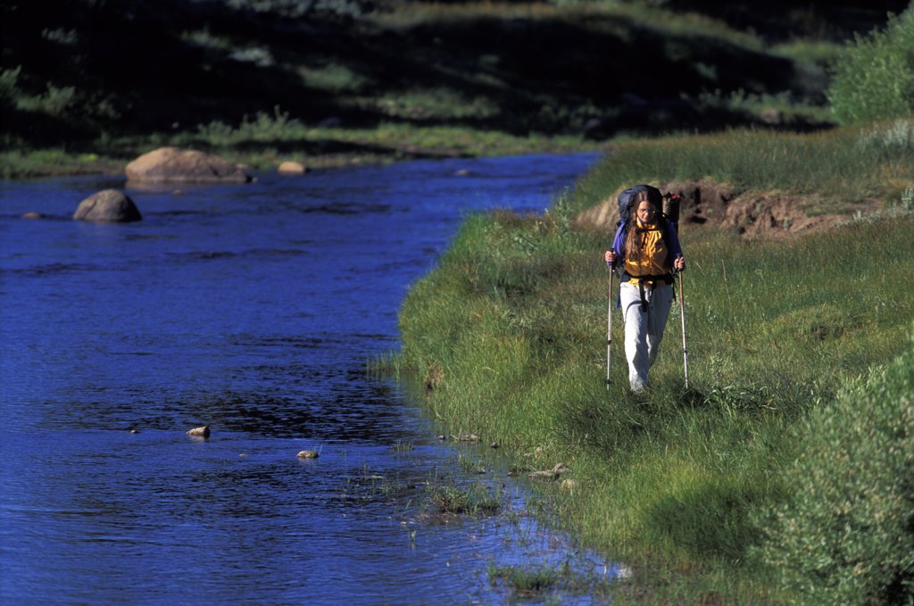 Stock Photo: 1778-10978 A woman trekking through a meadow next to a river