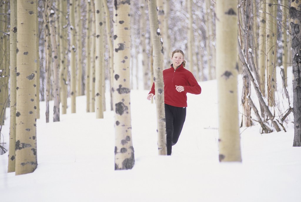 Woman running on snow covered trail : Stock Photo