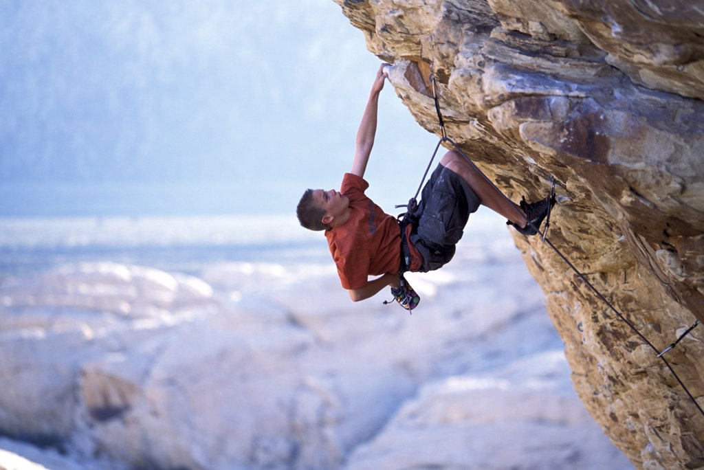 Stock Photo: 1778-11301 A young male climber on an overhanging route in the desert
