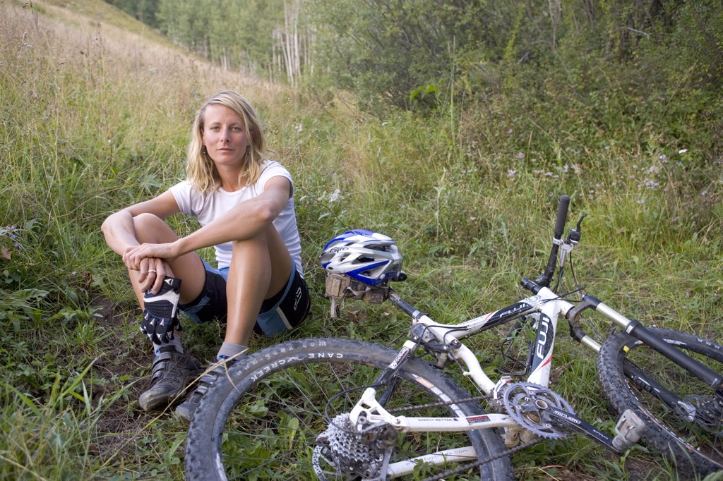 Stock Photo: 1778-11844 Woman mountain biker sitting in the grass by her bike, Crested Butte, Colorado