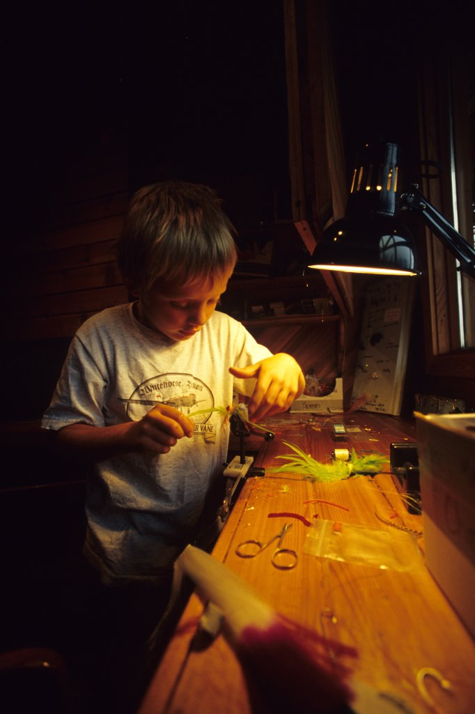 Stock Photo: 1778-12222 Young boy ties a fly-fishing fly at a fly-in fishing lodge in the Yukon Territory, Canada