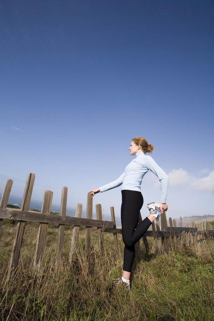 A young woman stretches before run along  the coastline of northern California near Mendocino, California : Stock Photo