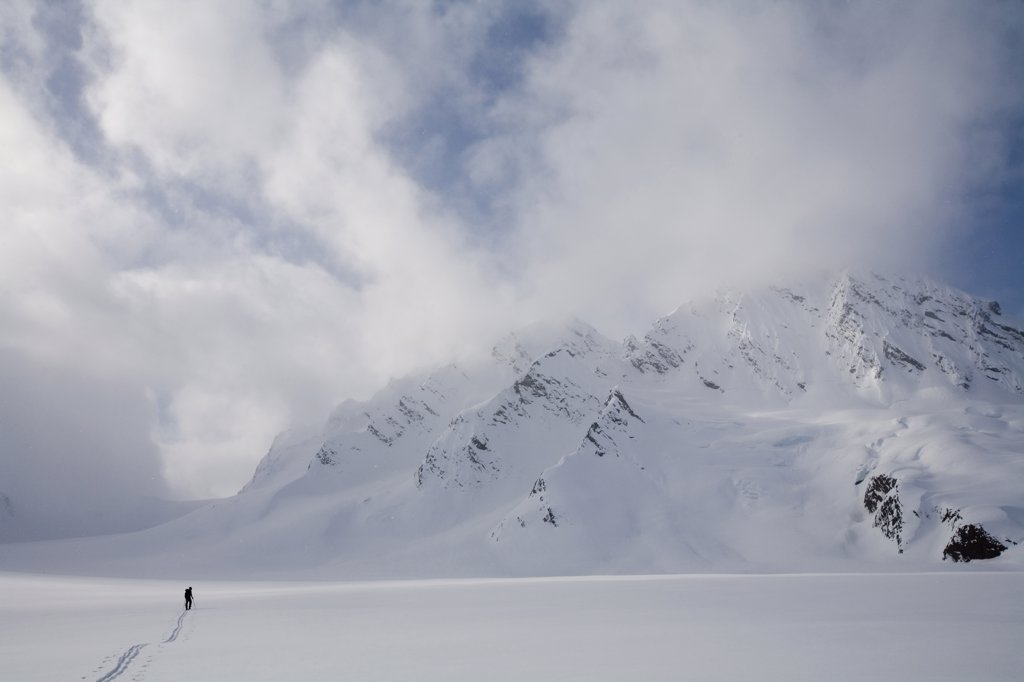 Stock Photo: 1778-12406 Backcountry skier crosses glacier under late day stormy sky