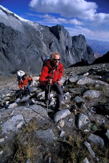 Two men hiking in the mountains with trekking poles in Cordillera Blanca, Peru : Stock Photo