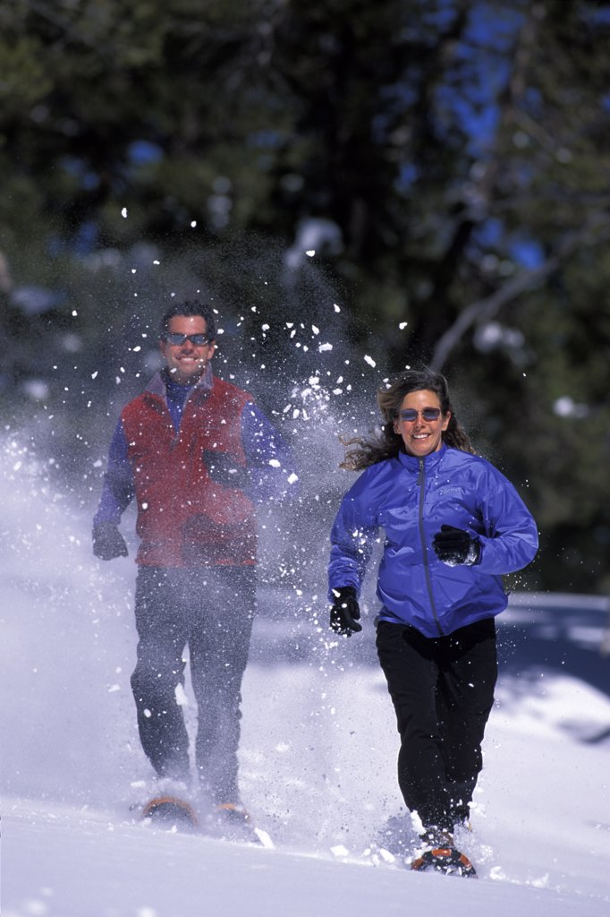 Man and a woman running on snowshoes in Lake Tahoe, California : Stock Photo