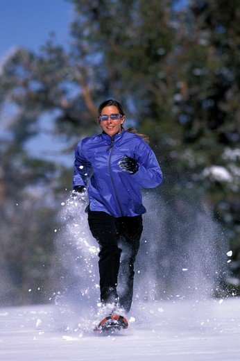 Stock Photo: 1778-13045 A woman running on snowshoes in Lake Tahoe, California