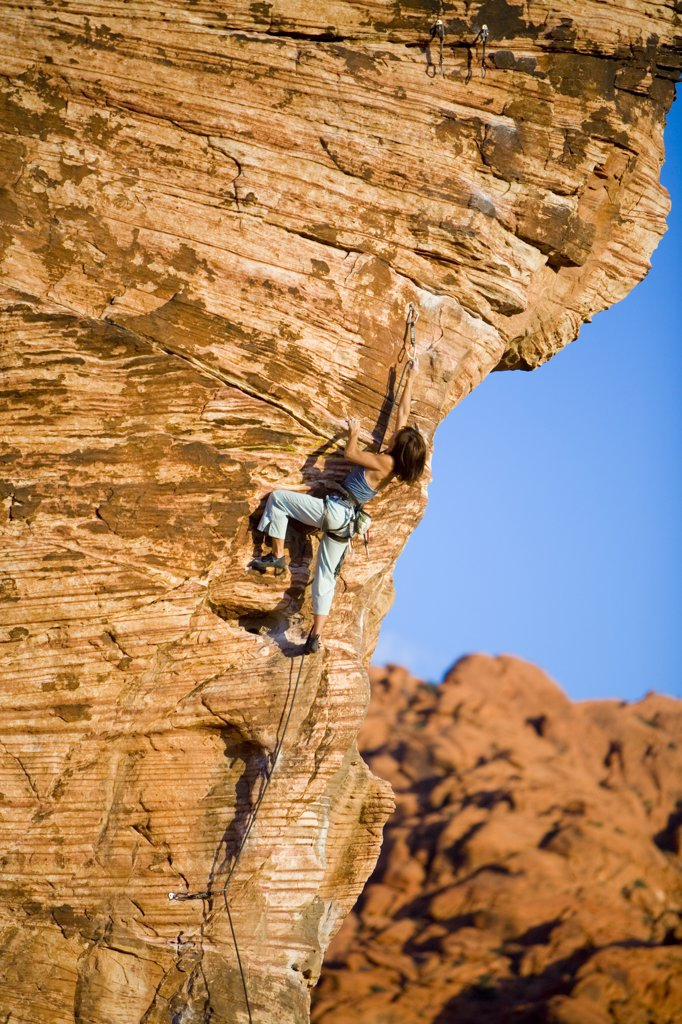 Stock Photo: 1778-13474 A women stretches to clip the draw on the crux while climbing