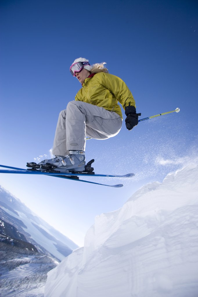 Stock Photo: 1778-13572 Woman skiing off cornice