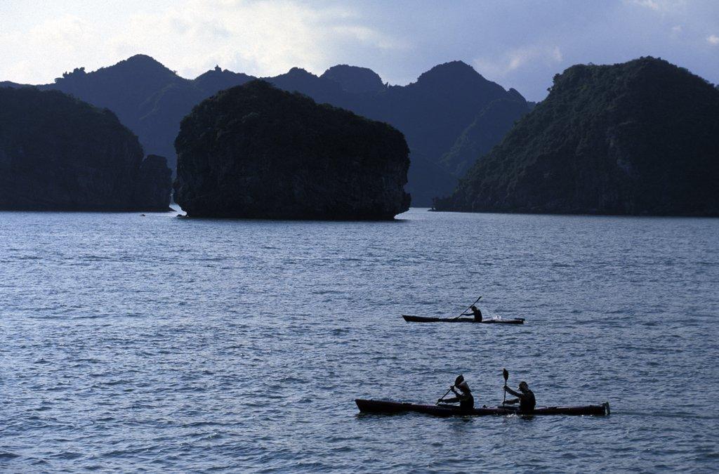 Stock Photo: 1778-13835 Racers paddle sea kayaks in Halong Bay during an adventure race in northern Vietnam (Silhouette)