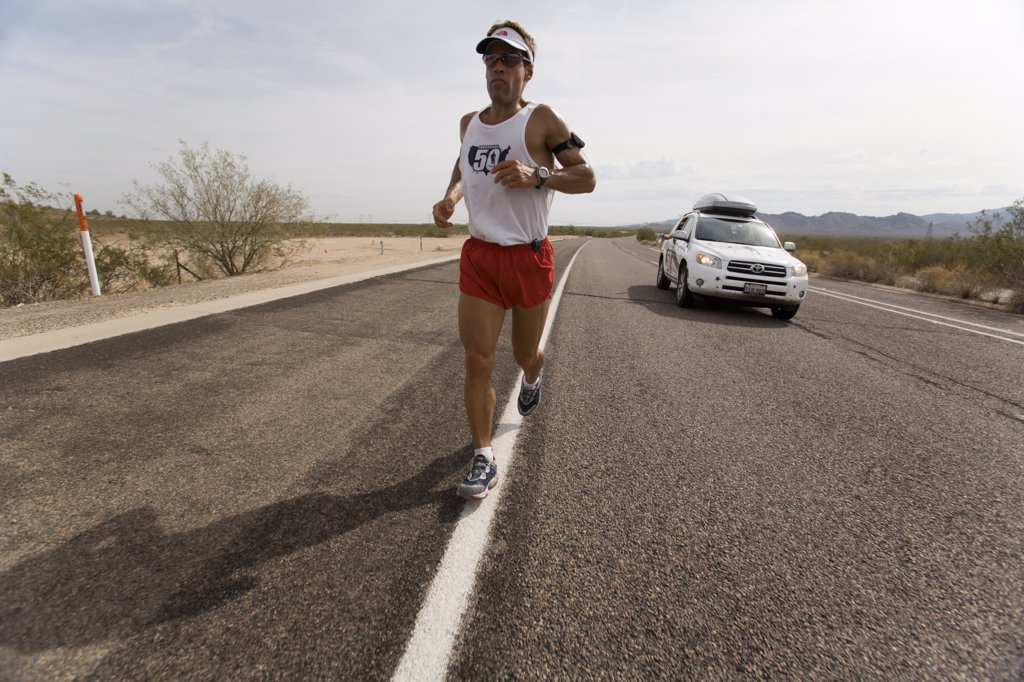 Stock Photo: 1778-14081 Man running on a highway with a support car during a marathon in Surprise, Arizona