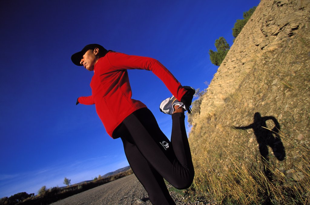 Attractive female runner stretching in tights with nice light : Stock Photo