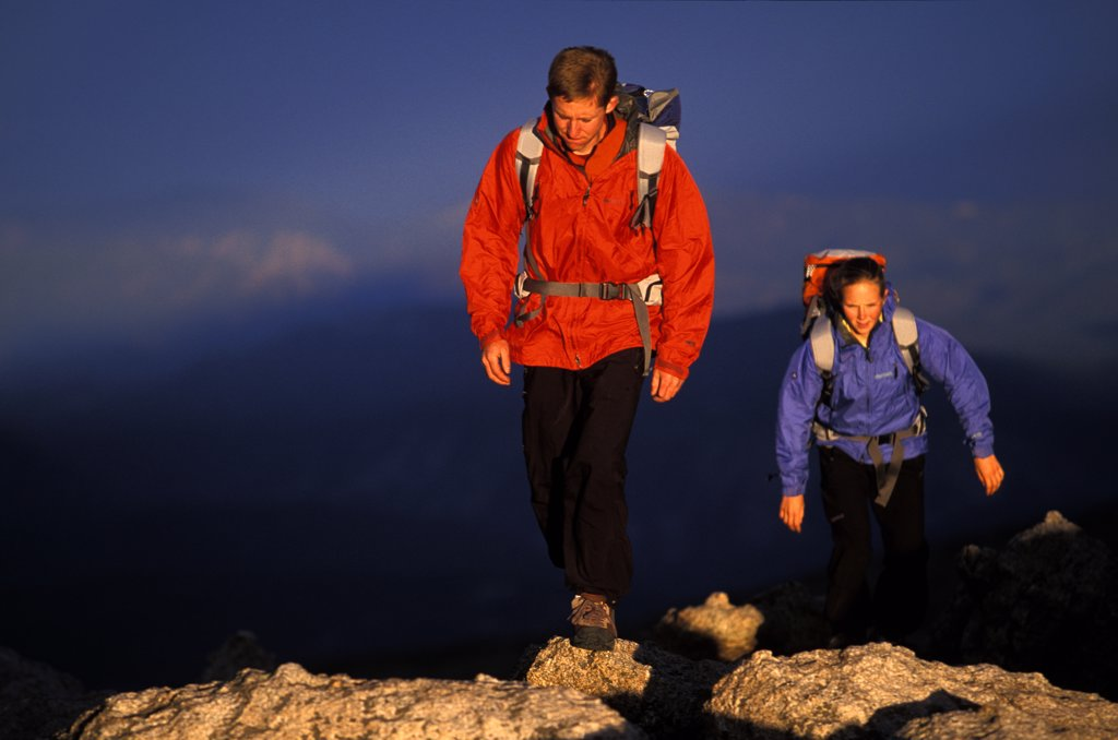 Stock Photo: 1778-8855 Man and woman hike up hill on a ridge