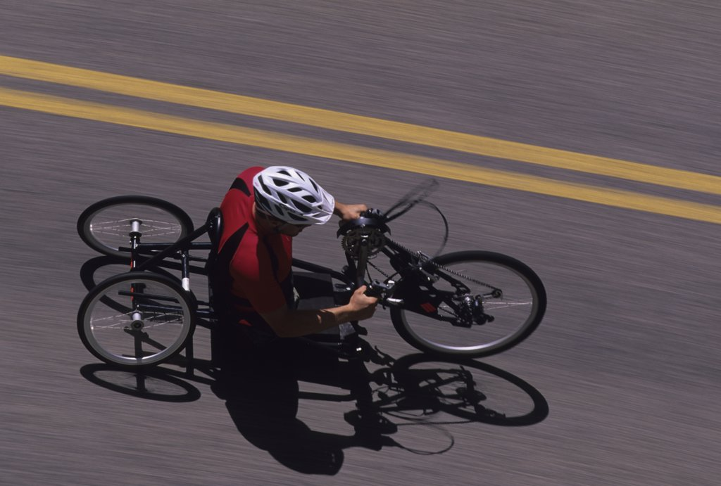 A young athlete with disabilities rides his hand road cycle : Stock Photo