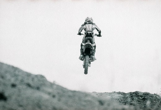 Stock Photo: 1778-9937 A young dirt bike rider jumps during a motorcross competition