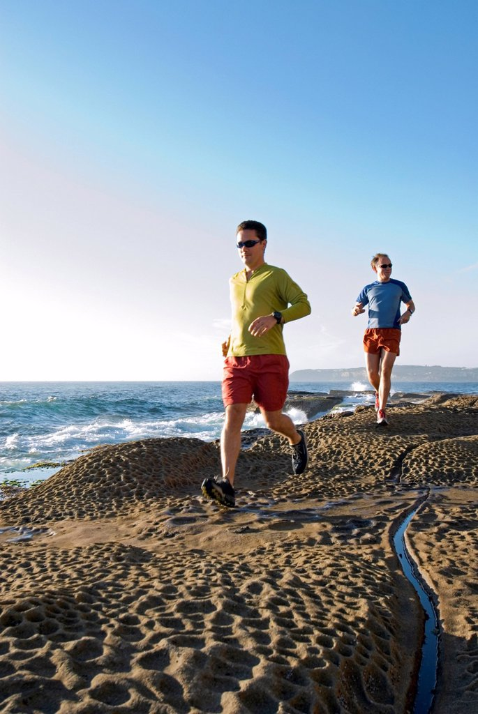 Stock Photo: 1778R-1481 Runners on rocky Pacific coast.