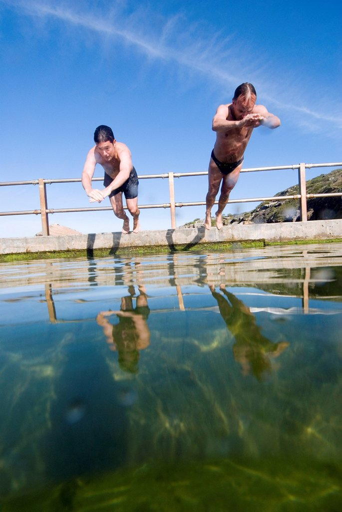 Men dive and swim in ocean rock pool. : Stock Photo