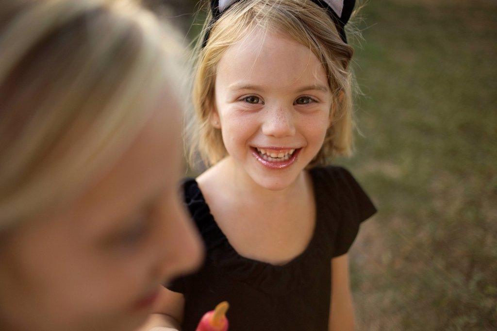 Stock Photo: 1778R-15744 Girl holding her cold treat, wearing cat ears, looks at the camera and smiles.