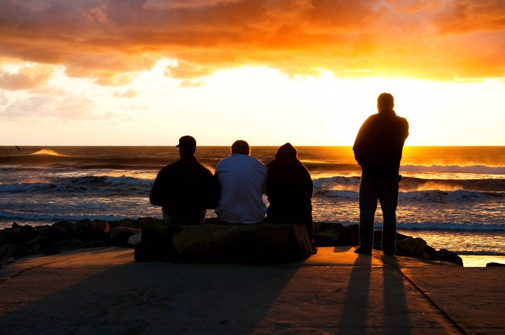 Stock Photo: 1778R-15882 Four men watching the sunset on the ocean on a stormy day in San Diego, California.