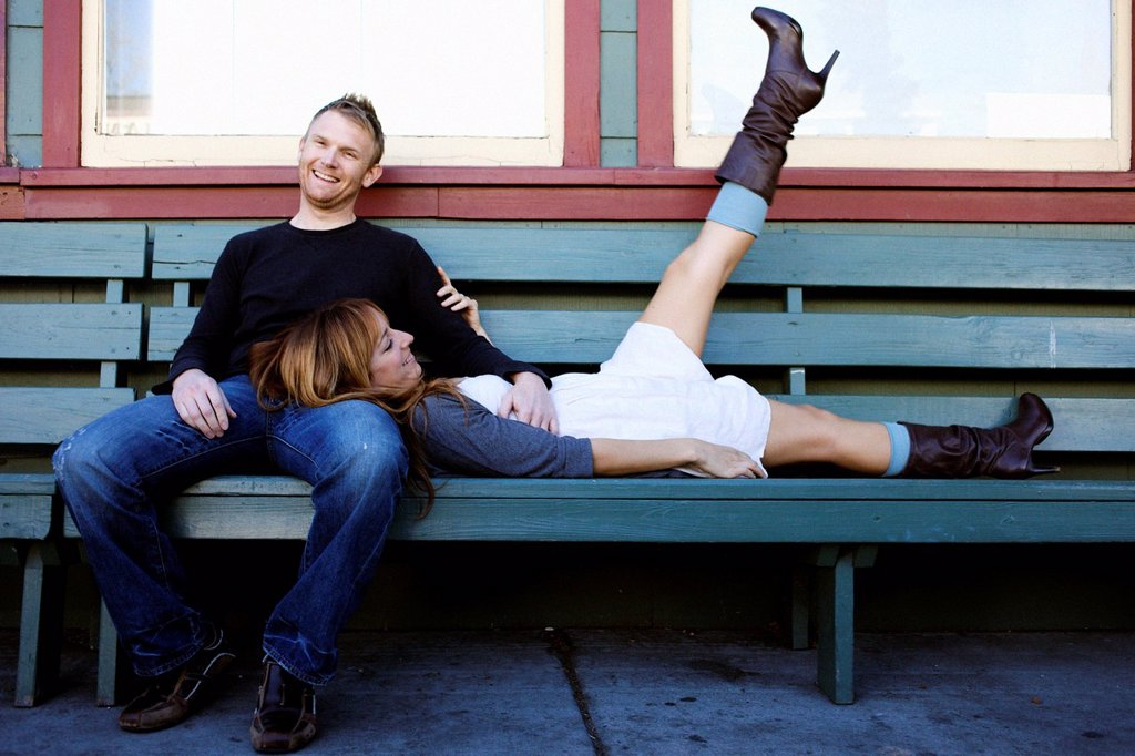 Stock Photo: 1778R-16067 Couple sits on a bench and smile.