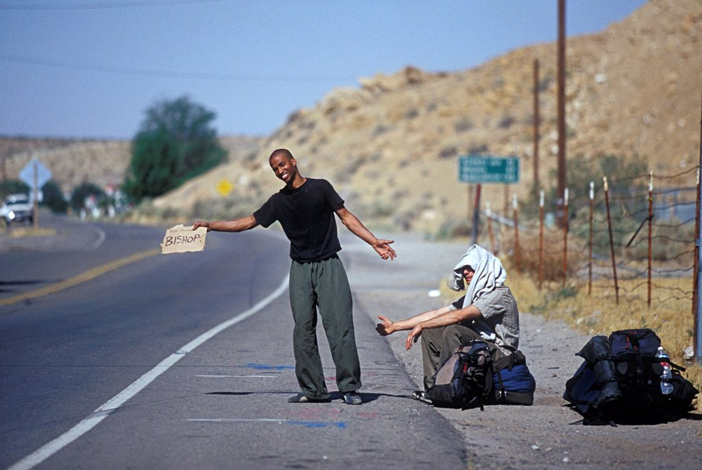 Two backpackers hitch hiking on the side of the road in the sun. : Stock Photo