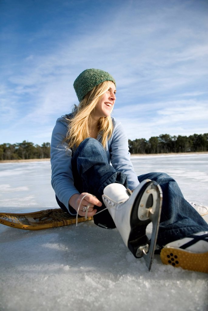 Young woman laces up ice skates. : Stock Photo