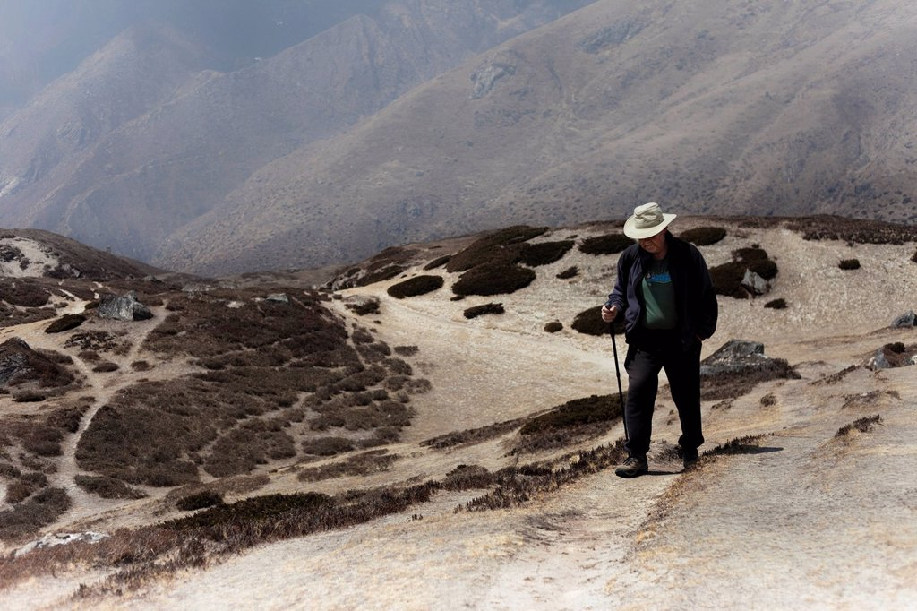 An unladen, male trekker walks to Amadablam base camp. : Stock Photo
