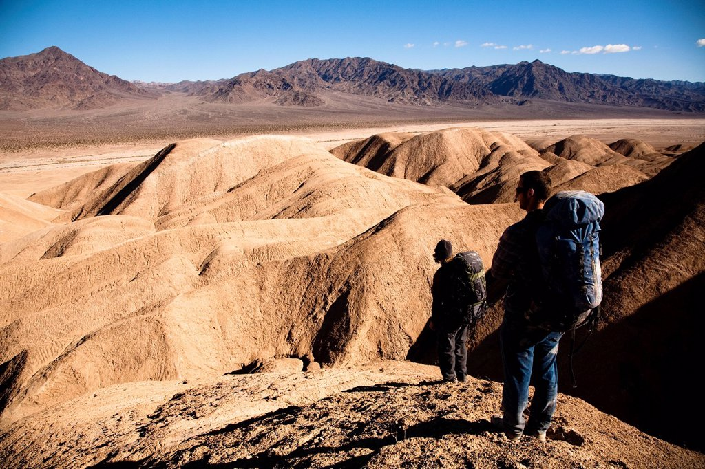 Two male hikers search to find the best route through Death Valley´s Confidence Hills, in California, while on backing packing. : Stock Photo