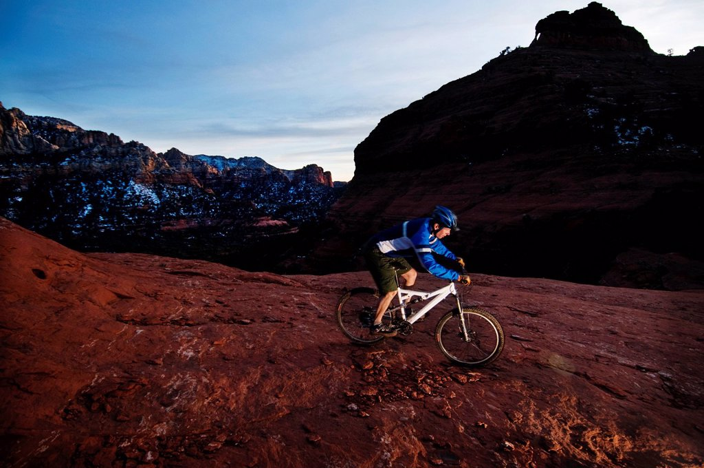 Stock Photo: 1778R-20544 A middle age man rides his mountain bike through the red rock country around Sedona, Az at sunset.