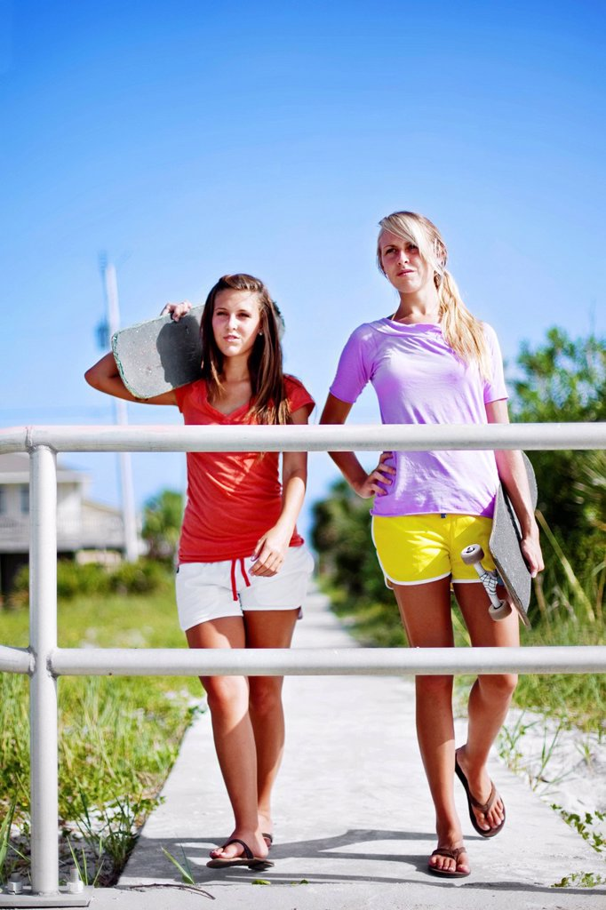 Two girls walk with their skateboards along a sidewalk towards Pensacola Beach, Florida. : Stock Photo