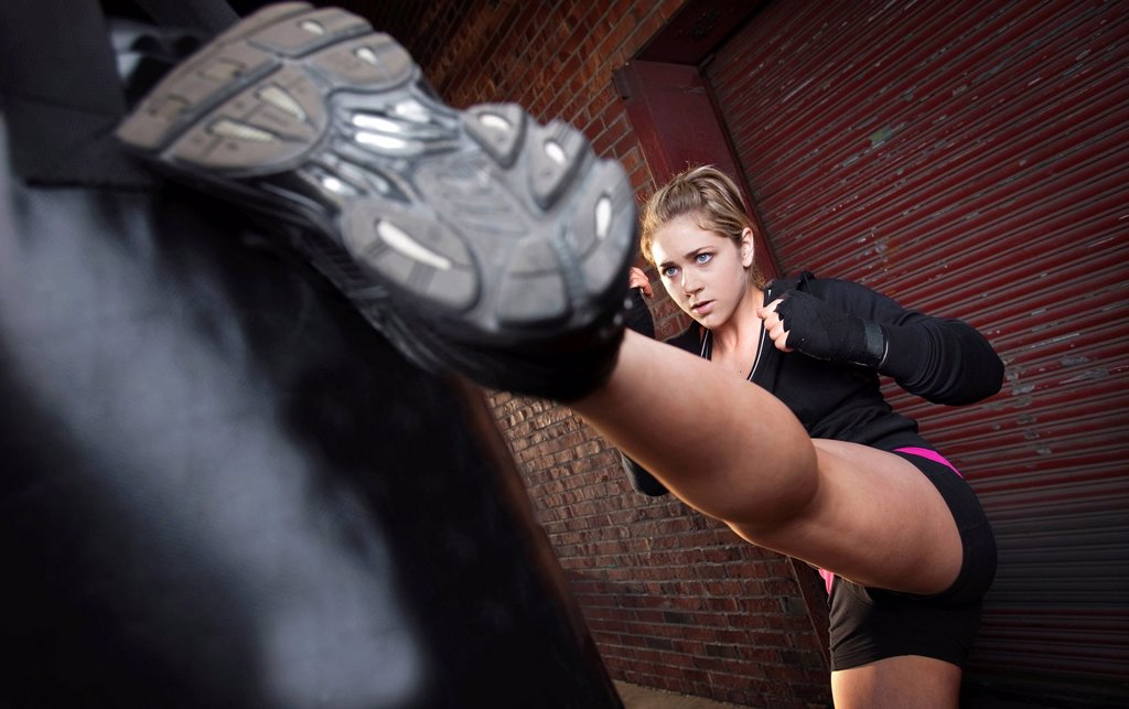 Stock Photo: 1778R-20959 A teenage girl high kicks a punching bag while training for mixed martial arts outside a warehouse in Birmingham, Alabama.