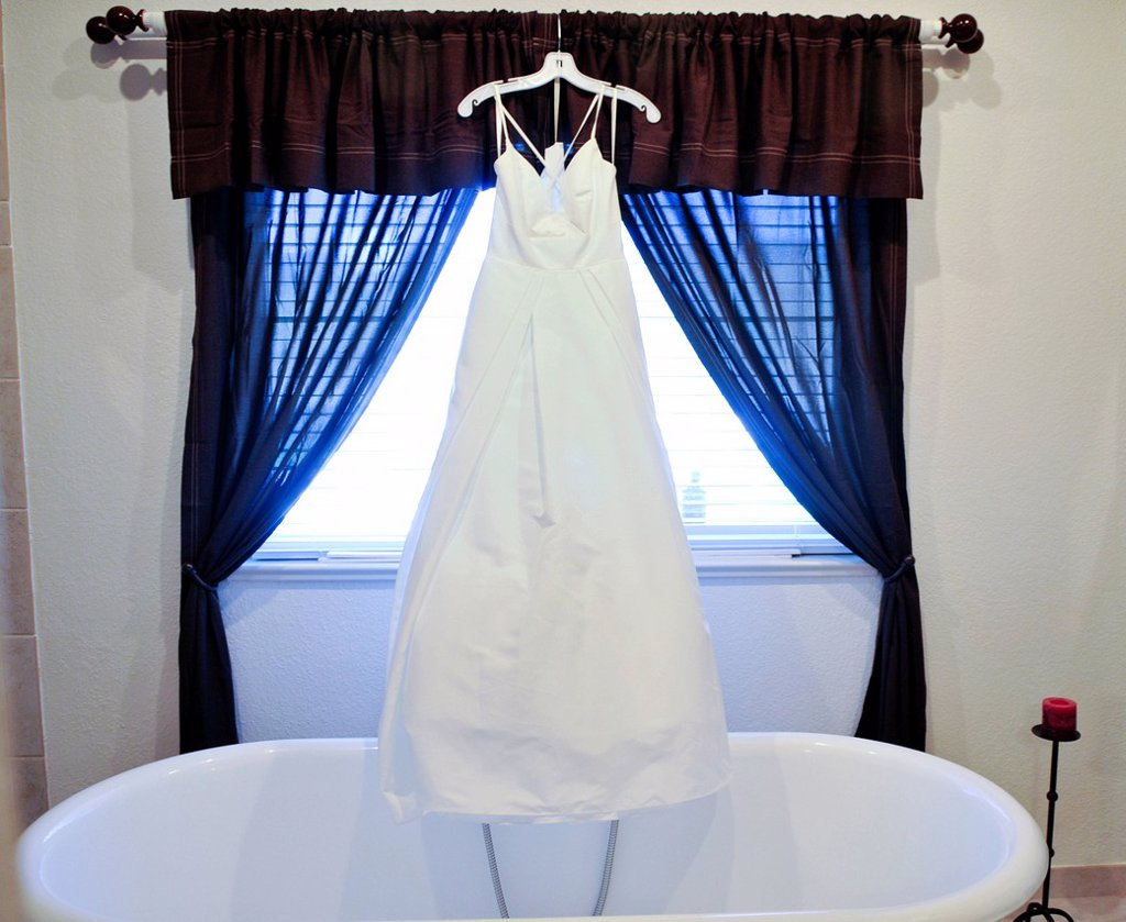 A wedding dress hangs in the bathroom before the big day in Dayton, Nevada. : Stock Photo