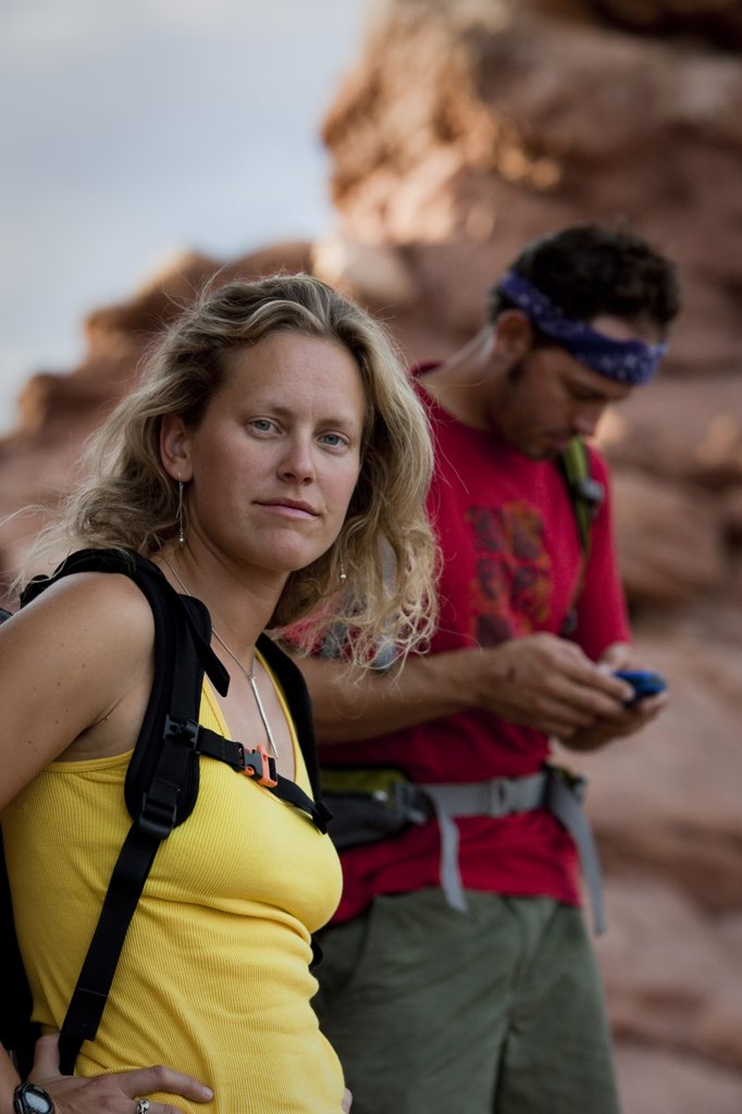 Stock Photo: 1778R-22167 A woman looks at the camera while a man in the background studies his GPS.