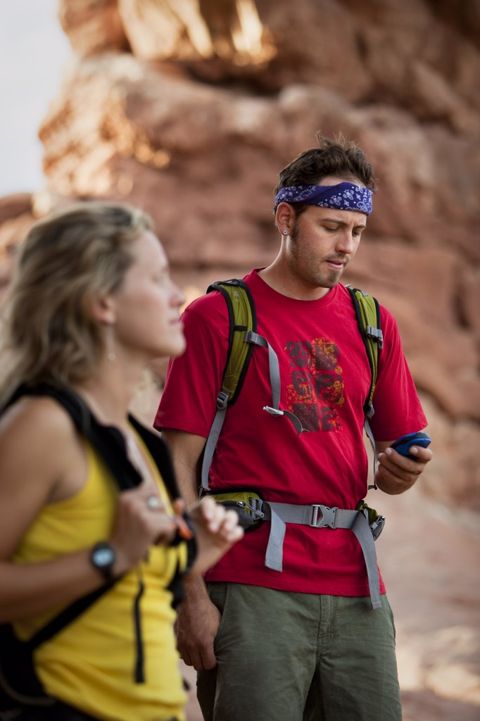 Stock Photo: 1778R-22168 A man with backpack on looks at his GPS while an out of focus woman in the foreground looks on.