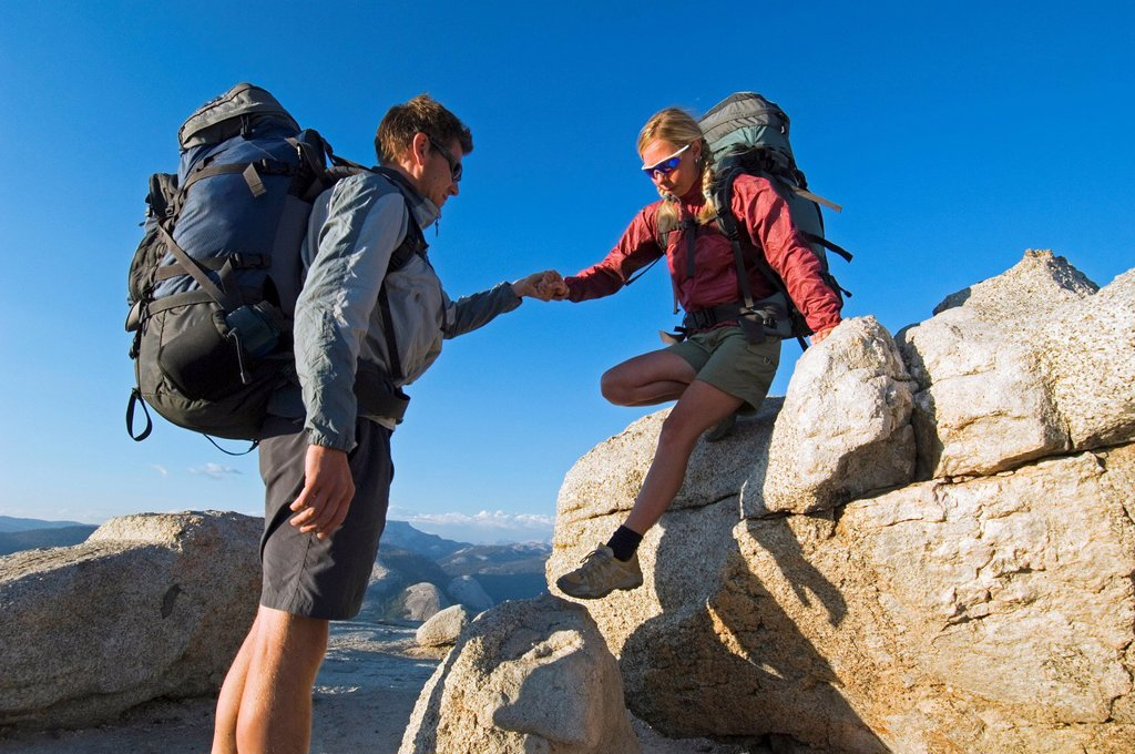 Hiker being helped off of rock. : Stock Photo