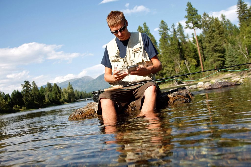 Stock Photo: 1778R-22210 A teenage boy sits on a rock as he chooses a fly while fly fishing on the Swan River near Bigfork, Montana.