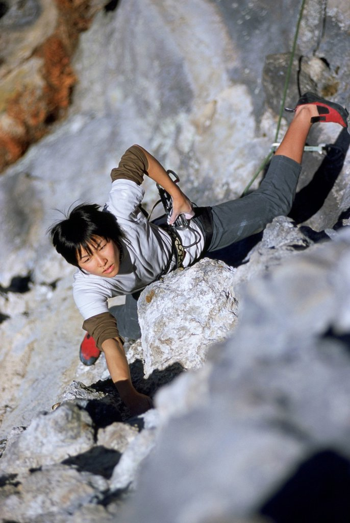 A girl climbs steep rock in Japan. : Stock Photo