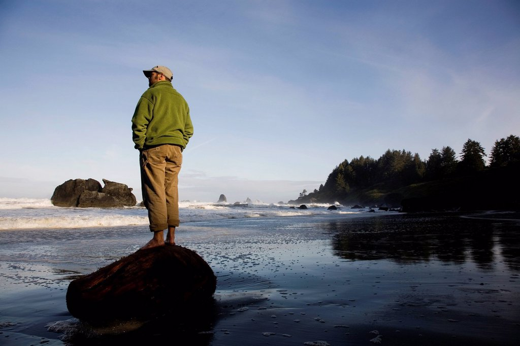 Stock Photo: 1778R-22477 REDWOODS NATIONAL PARK, CALIFORNIA. A man stands alone on a piece of wood on the beach near Redwood National Park.