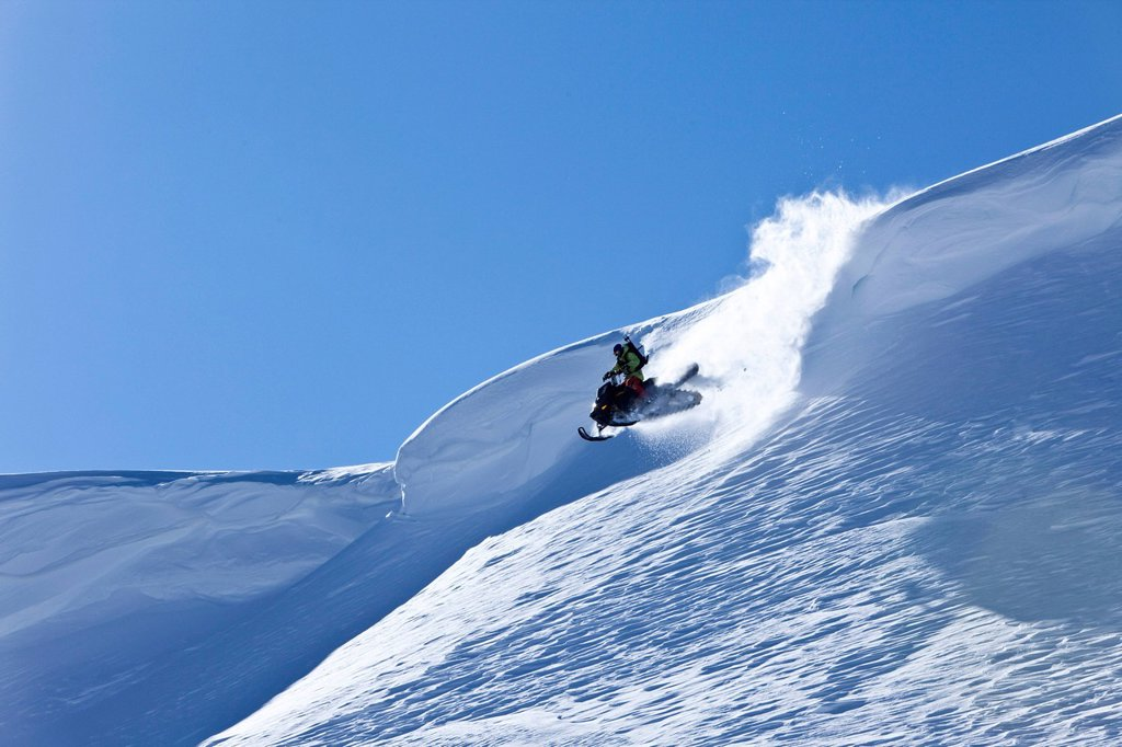 A snowmobiler jumping off a cornice on a sunny winter day in Montana. : Stock Photo