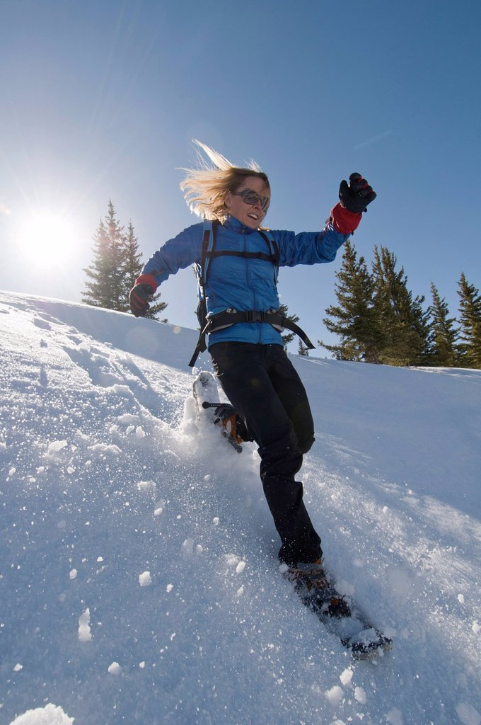A woman snowshoeing on Molas Pass, San Juan National Forest, Silverton, Colorado backlit. : Stock Photo