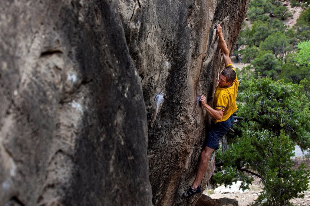Stock Photo: 1778R-23280 A man crimps hard while stretched out on a boulder problem at Joes Valley Utah.