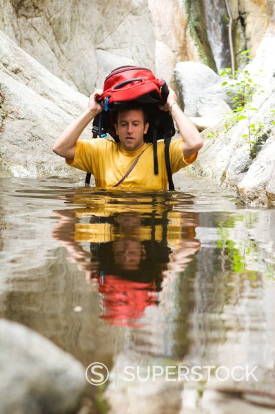 Stock Photo: 1778R-2336 A man canyoneering wades in water.