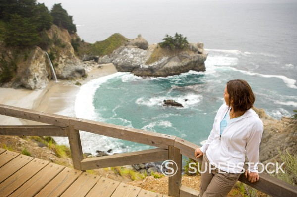 Woman crosses bridge while exploring. : Stock Photo
